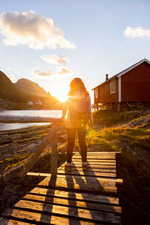 Woman tourist with a backpack looks at the sunset on the Lofoten Islands, Norway