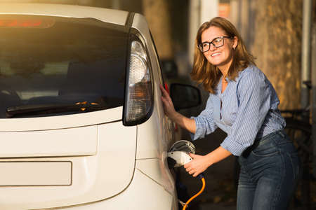 Woman is charging carsharing electric car.