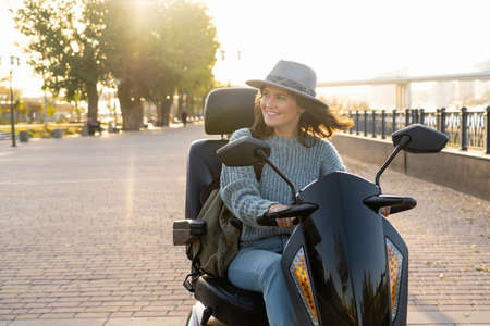 Woman tourist riding a four wheel mobility electric scooter on a city street. Standard-Bild