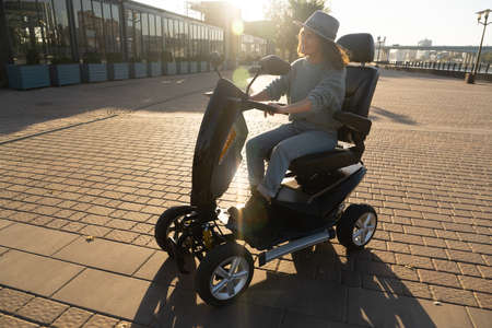 Woman tourist riding a four wheel mobility electric scooter on a city street.