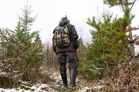 Hunter with a gun and a backpack in the winter forest