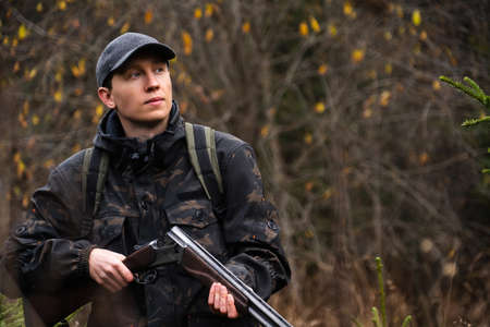 Hunter with a gun and a backpack Banco de Imagens