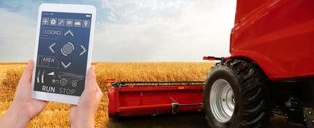 Farmer uses a digital tablet to control autonomous harvester. Smart farming concept