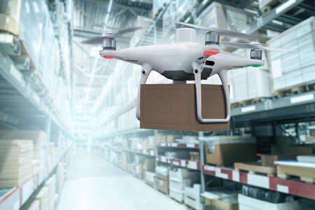 Drone with a package in a distribution warehouse Stockfoto