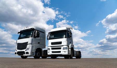 Two white trucks against the blue sky