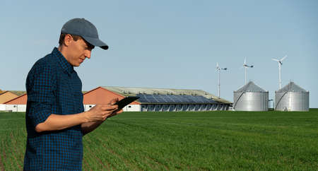 Farmer with tablet computer on a background of modern dairy farm using renewable energy, solar panels and wind turbines Stock fotó