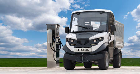 City delivery electric truck with charging station on a background of green field and blue sky. Clean mobility concept Stockfoto