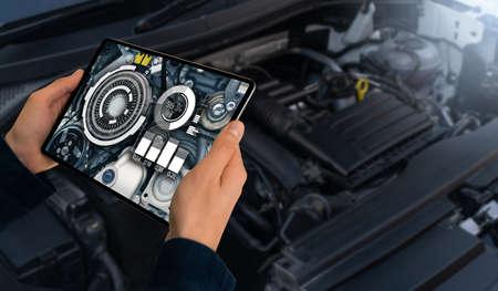 Serviceman repairing a car using augmented reality application.
