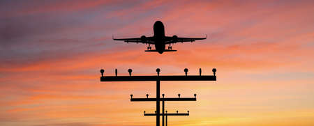 Silhouette of a plane landing at the airport