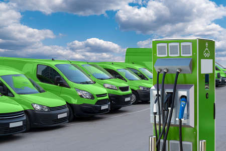Electric vehicles charging station on a background of a row of vans