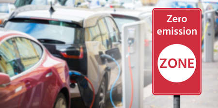 Road sign Zero emission ZONE on a background of electric cars. Clean mobility concept Stock Photo