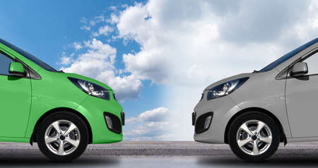 A green electric car in front of a gray petrol car. Stock Photo