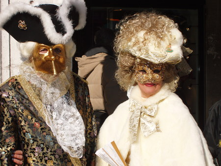 Parade of masks at Piazza San Marco Venice, a couple of 18th century nibbles dressed in gold, black and white.