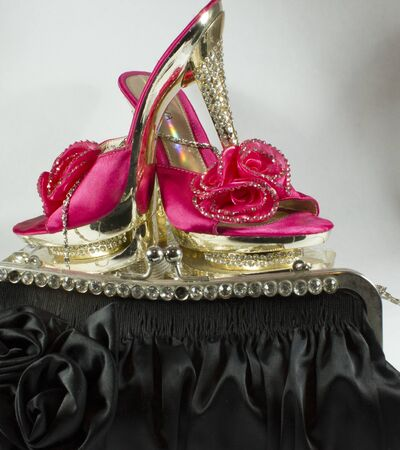 Intense pink shoes with heels studded with glitter, enriched with flower. With a black handbag in front with flowers and glitter