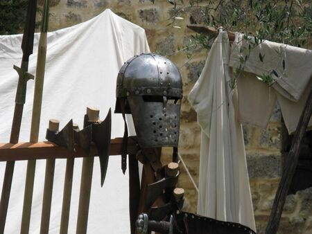 medieval weapons inside a castle helmet in the foreground and sharp axes