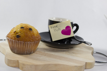 cup of black coffee, chocolate muffin, and ticket with heart for mom Stock Photo