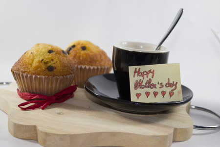 white background, with breakfast set for mother's day, on a tray there are two muffins with red ribbon, cup of coffee is greeting card with little hear