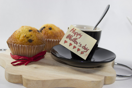 best wishes mom !!! Breakfast dedicated to mothers with a coffee cup, two muffins with red ribbon and a special greeting card Standard-Bild