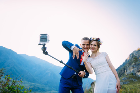 Beautiful young wedding couple making selfie and kissing on the background of mountains Standard-Bild