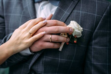 Hands of the bride and groom with elegant manicure, close-up. Wedding rings of the newlyweds, couple on wedding day, touching moment.