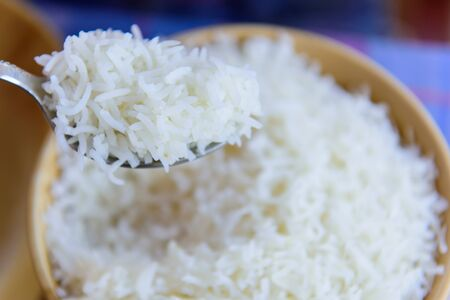 white steam rice on a spoon macro detail and background Stock fotó