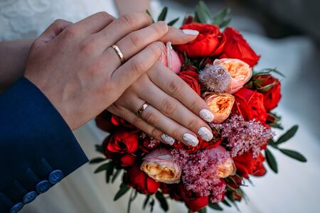 Newlywed couple holding hands and displaying wedding rings, close up. Hands and rings on the background of wedding bouquet.