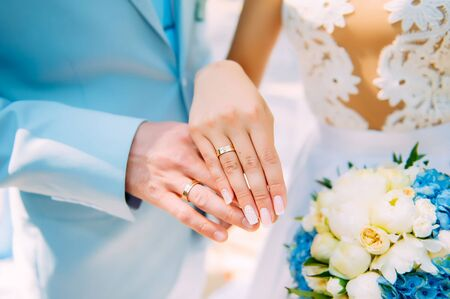 Hands of newlyweds with beautiful gold rings, close-up. White bridesmaid dress, bouquet, stylish manicure. Perfect wedding ceremony.
