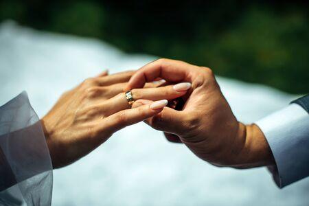 Bräutigam legte goldenen Ehering auf den Finger der Braut, Nahaufnahme. Die Hochzeitszeremonie, Austausch von Ringen.