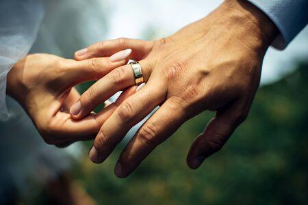 Junge Braut legte dem Bräutigam einen goldenen Ehering an den Finger, Nahaufnahme. Hochzeitszeremonie, Ringtausch. An der Hand des Mannes, der einen Ehering trägt.