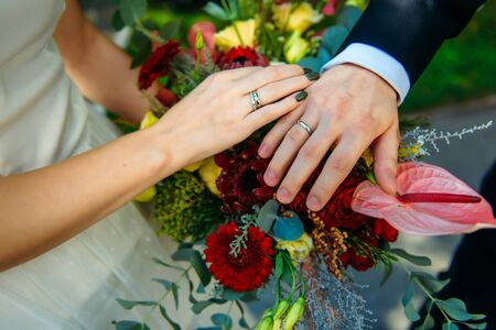 Newlywed couple holding hands and displaying wedding rings, close up. Hands and rings on the background of wedding bouquet. Zdjęcie Seryjne - 133077498