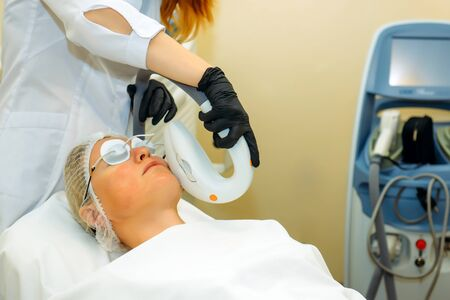 Beautiful woman in cosmetic clinic during photo rejuvenation procedure. Anti acne phototherapy with professional equipment. Laser face skin treatment in a beauty salon. Hardware cosmetology.
