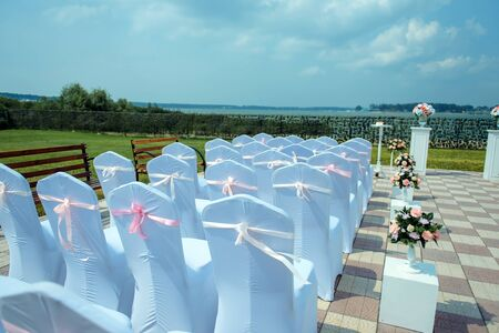 Exit registration of the newlyweds, wedding ceremony under open sky. Seating guests overlooking the river. Rows of chairs with white capes, wedding arch, floral design.