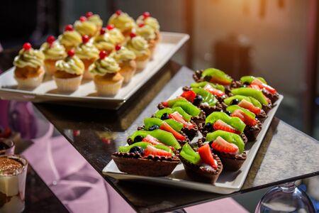 Kuchen mit frischem Obst und Beeren auf dem Feiertagstisch, Nahaufnahme. Cupcakes mit Sahne. Süßer Tisch beim Galadinner. Standard-Bild