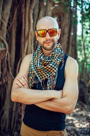 Portrait of stylish young bald guy in sunglasses on blurry background outdoor. Attractive cheerful man poses for the camera and smiles.