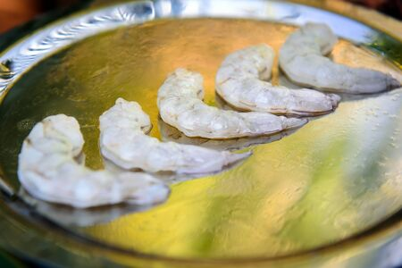 King prawns peeled from shell lay in a row on platter before cooking in seafood restaurant. Tiger shrimp without head, close-up. Sea delicacies, protein food. Banque d'images
