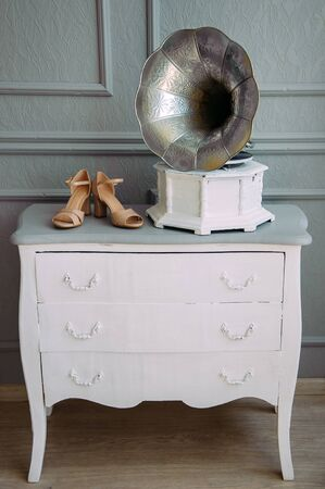 Retro photo-gramophone on a white wooden dresser, standing next to beige women's shoes with heels. Wedding theme, Studio shooting.