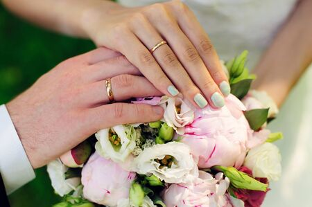 Hands of newlyweds on the background of wedding bouquet. Gold wedding rings on the finger of bride and groom, close-up. Concept of a wedding celebration. Stock Photo