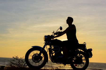 Silhouette of guy on motorcycle on sunset background. Young biker are sitting on motorcycle, face in profile. Moto trip on the seaside, freedom and active lifestyle.