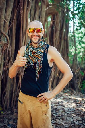 Portrait of stylish young bald guy in sunglasses on blurry background outdoor. Attractive, cheerful man poses for the camera, smiles, and gives thumbs-up.