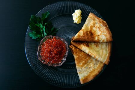 Traditional thin Russian pancakes with red caviar, butter and greens on a black wooden background. Stock Photo