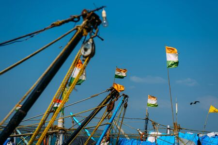 Close-up view of the wooden masts of fishing boats in bay, Goa, India. On the old masts fluttering Indian flags and hanging lifebuoys. Indian tricolor, independence Day.