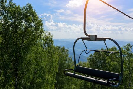 Lift on the background of mountains and green hills on sunny summer day. Empty bench of ski lift, tourism closed off quarantine. Inactive resorts.