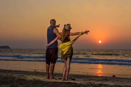 Lovers hugging against sunset on the sea. Young couple standing on a beach and admiring to sunset. Stockfoto