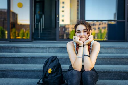 Beautiful College student girl sitting on the steps and laughing looking at camera. Portrait of a cheerful high school girl with two long braids.