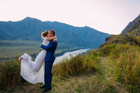 Young newly wed couple, bride and groom kissing, hugging on perfect view of mountains, blue sky