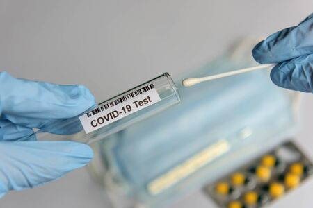 Hands in medical gloves holding COVID-19 swab. Test tube for taking patient sample, PCR DNA testing protocol process. Nasal swab laboratory test in hospital lab. Stock Photo