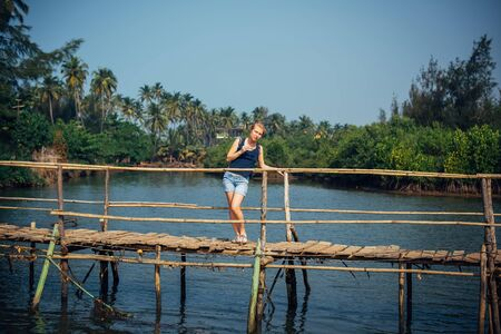 A female tourist in denim shorts with short haircut on sunny tropical day. Young pretty girl stands on wooden bridge over small river against palm jungle and blue sky. Trips to picturesque places.
