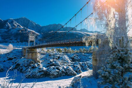 Big road bridge over frozen river against a backdrop of snow-capped mountain slopes and bright blue sky on a sunny winter day. Stunning frosty landscape in the Altai mountains. Stock Photo