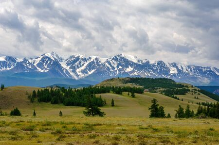 Panoramic view of the North-Chui mountain range under cloudy sky. Kurai steppe and snow-capped peaks of Altai mountains. Stock Photo