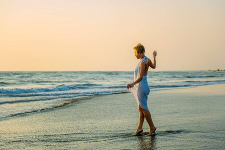 Charming slender blonde in stylish dress stands in waves on the sea. Young woman walks barefoot along the surf and enjoys the rest. Female beauty and naturalness.